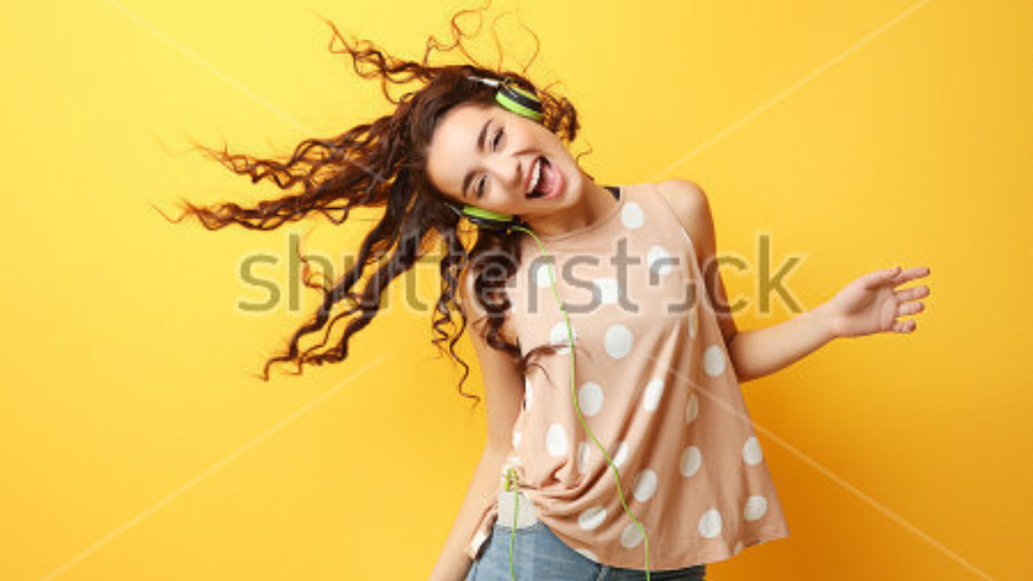 Stock Photo Beautiful Young Woman In Headphones Listening To Music And Dancing On Yellow Background 585033697